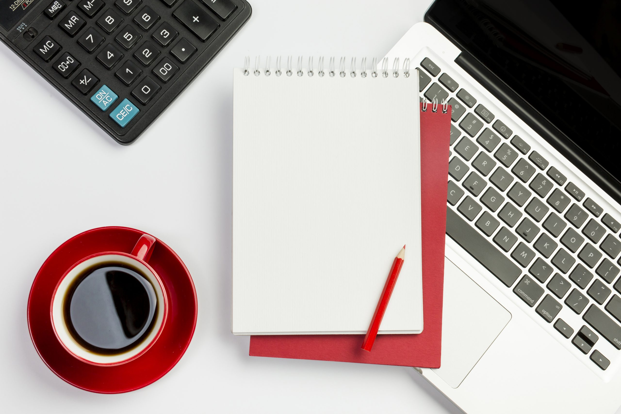 red-coffee-cup-calculator-spiral-notepad-pencil-laptop-white-background